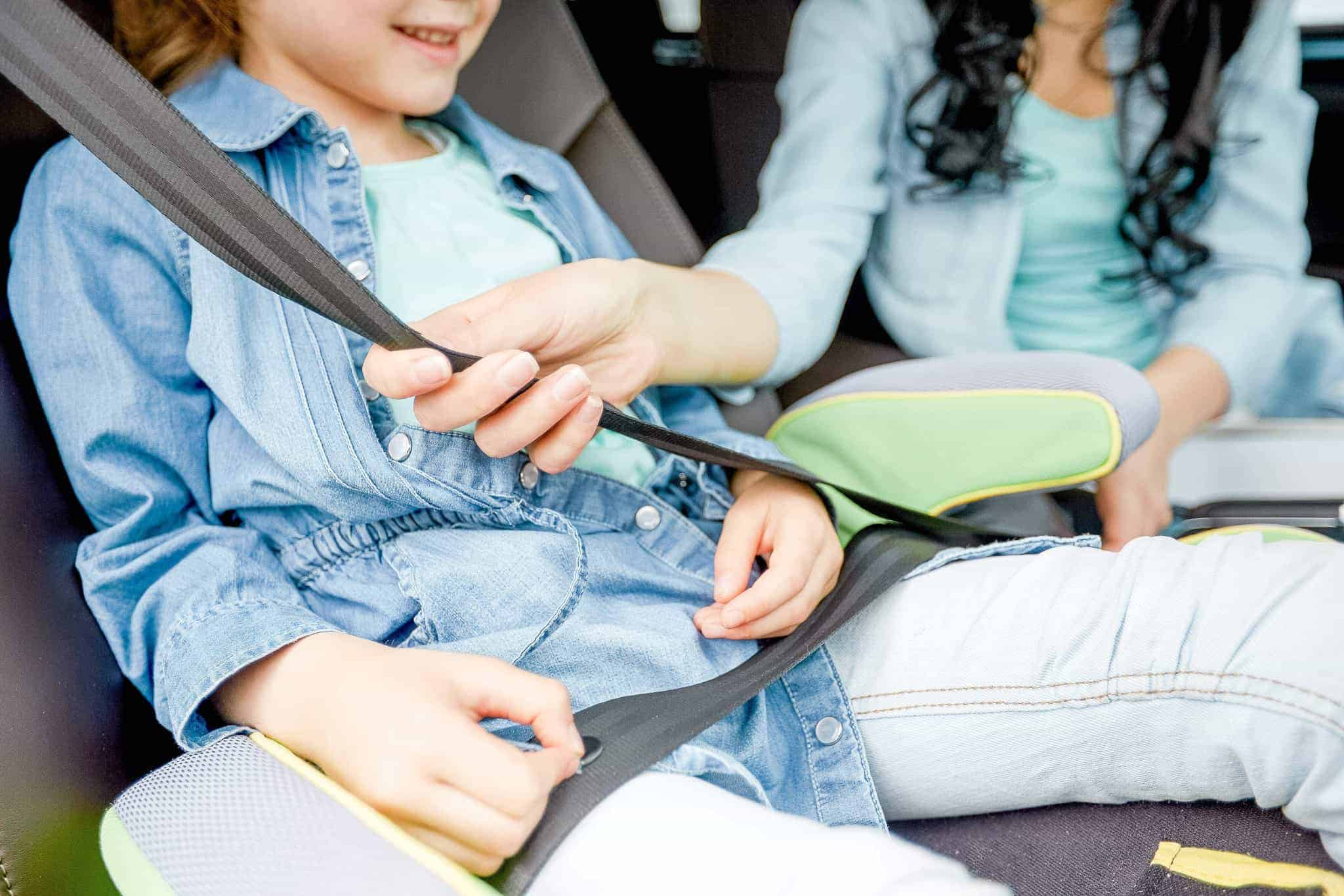 child in booster seat in car