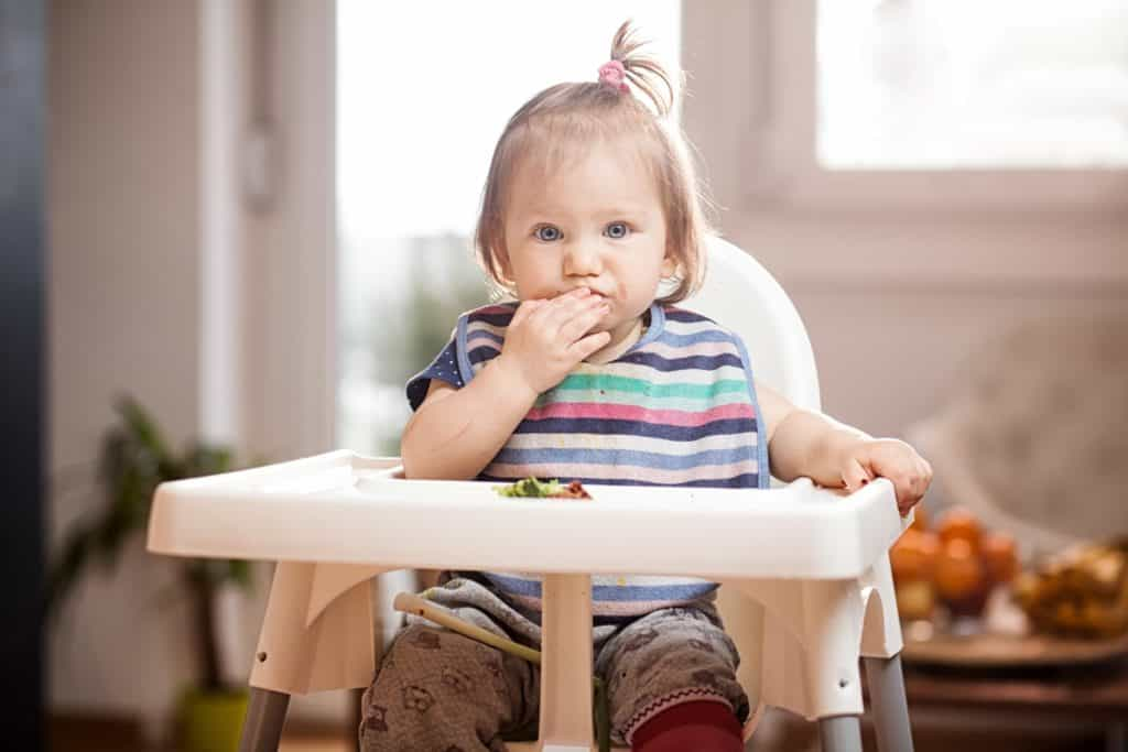 baby feeding herself in high chair